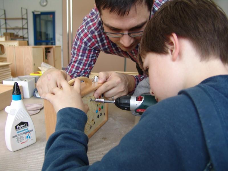 Rainer Brang schraubt mit seinem Sohn Martin einen MP3-Player aus Holz zusammen. FOTO: Winzki